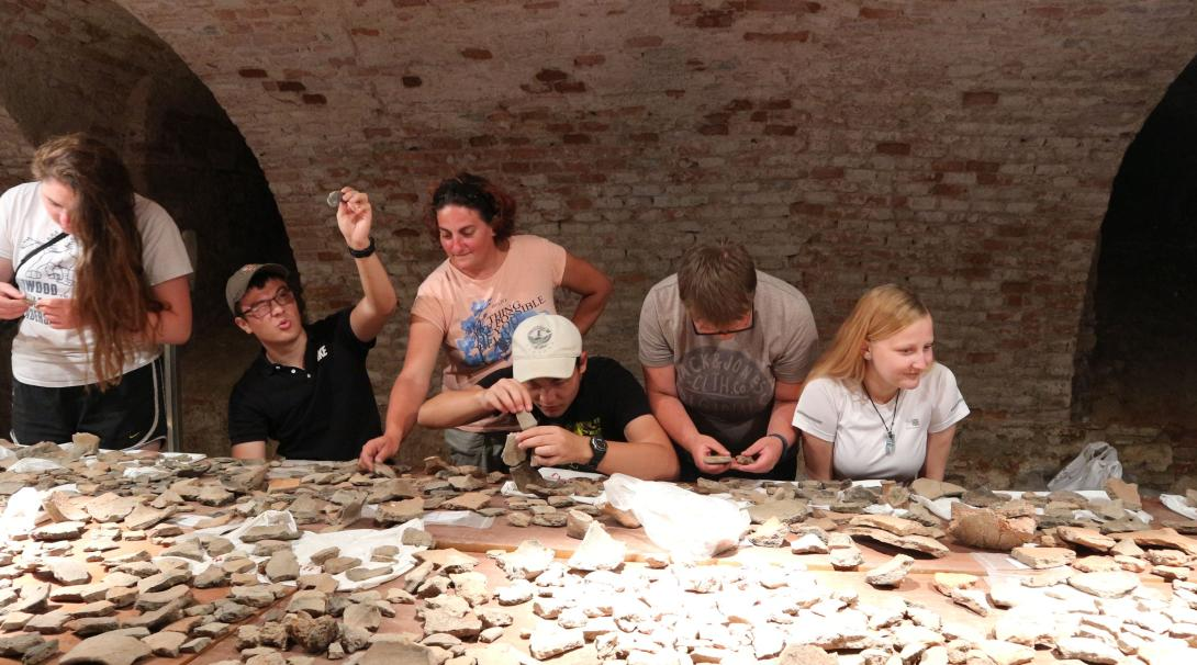 Archaeology volunteers in Romania look at the ceramic artefacts uncovered at their dig site in Eastern Europe.